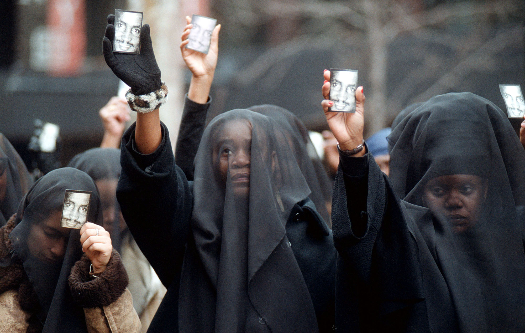 Women wearing veils of mourning hold cards with the image of Amadou Diallo before the start of a prayer vigil outside the United Nations February 27, 2000 in New York. The Rev. Al Sharpton is holding the vigil to protest the acquittal of four white New York City police officers charged in the February 1999 shooting death of Diallo. (Photo by Spencer Platt/Getty Images)