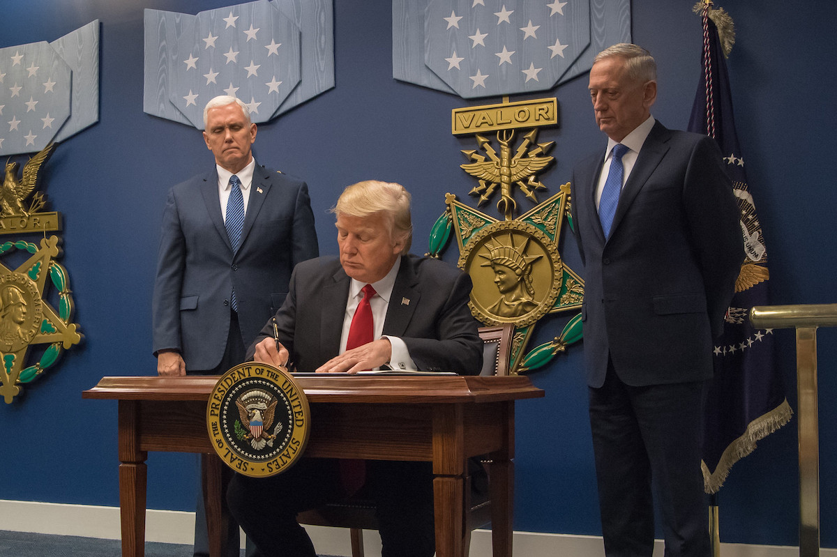 U.S. President Donald Trump signing the order at the Pentagon, with Vice President Mike Pence (left) and Secretary of Defense Jim Mattis. Source: U.S. Secretary of Defense Flickr