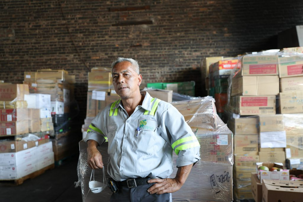 A man stands amidst stacks of boxes in a warehouse.