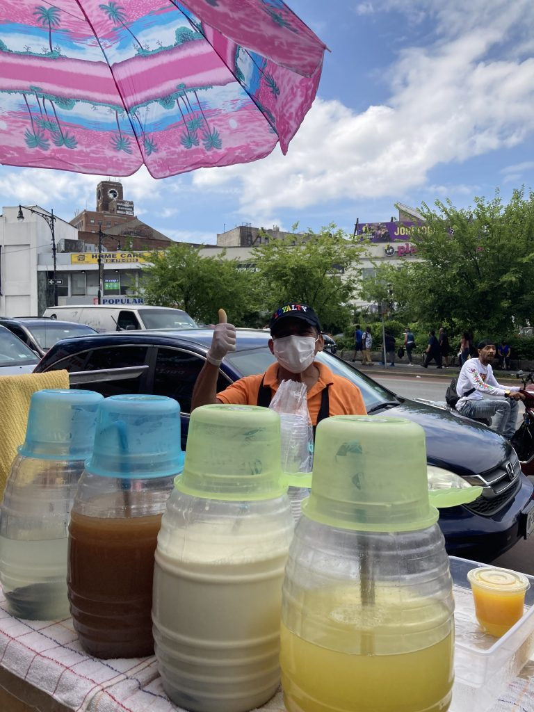 Lucio stands on a street in the Bronx wearing a mask with the drinks he sells in front of him.