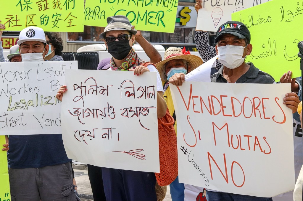 Street vendors hold signs in Spanish, English and other languages in a protest against undue fines in the Bronx.